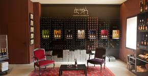 salle de dégustation, mur de bouteilles, deux fauteuils colorés